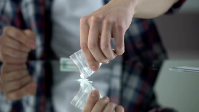 Young man preparing cocaine to snort it through rolled-up dollar, drug addiction video