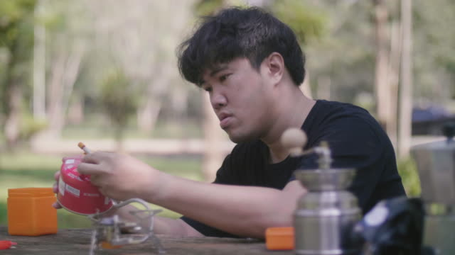 Young man preparing to make coffee at wooden table in the nature.