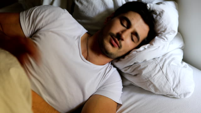 young man pulling blanket on bed at home - kołdra filmów i materiałów b-roll