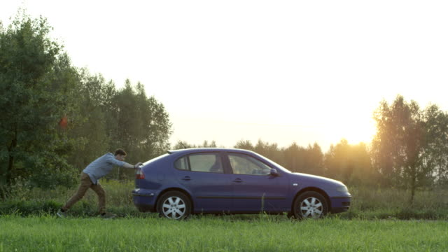 Young Man Pushing the Car Seen From the Side. Sunset