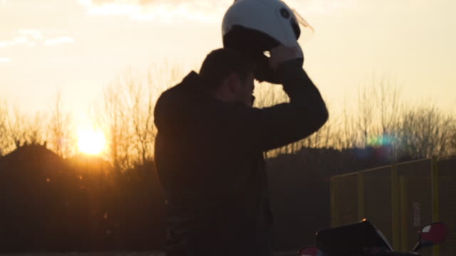 A young man puts a helmet to go on a journey
