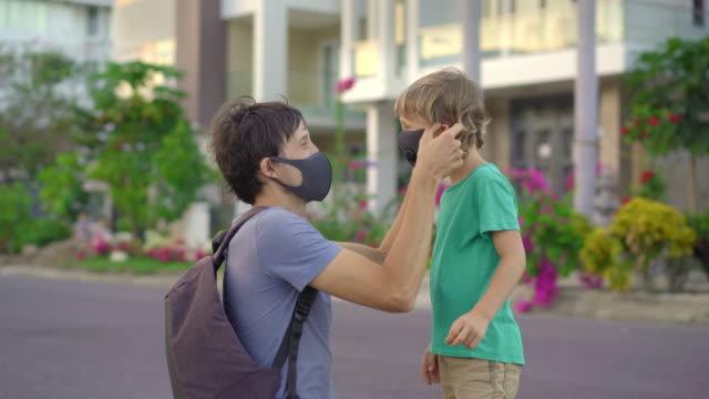 ein junger mann legt seinem sohn eine gewebemaske auf. modische gesichtsmasken. soziales entsungskonzept - textilien stock-videos und b-roll-filmmaterial