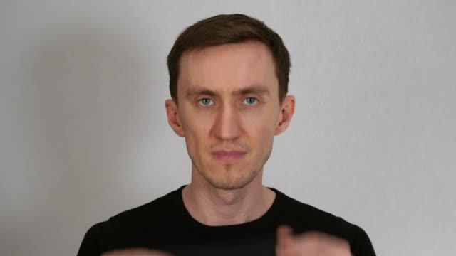 vídeos de stock, filmes e b-roll de um jovem coloca uma máscara médica preta em um fundo cinza - camiseta preta
