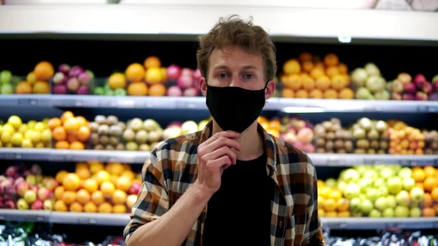 A young man puts on a tissue mask to protect against the epidemic, a close-up portrait. Protection from the coronavirus pandemic. Standing against grocery shelves video