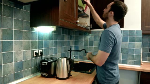 Hombre joven de poner platos en la cocina - vídeo