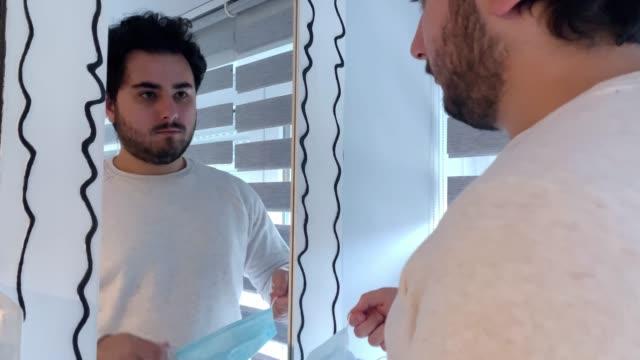 stockvideo's en b-roll-footage met jonge mens die op een gezichtsmasker zet - mirror mask