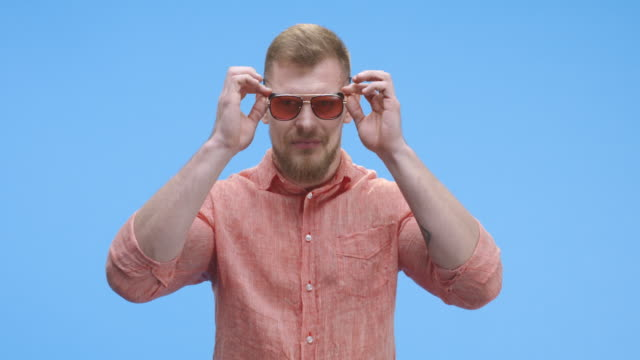 Young man putting on sunglasses