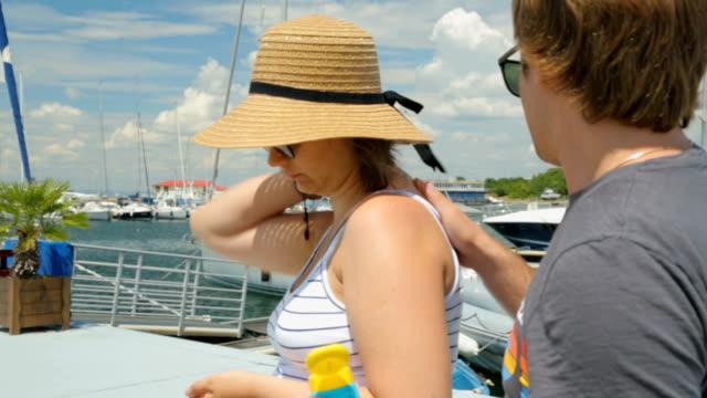 vidéos et rushes de jeune homme mettre un écran solaire sur les épaules sa femme - chapeau