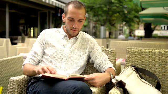 Young man reading a book in a cafe video