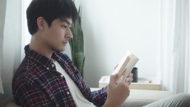 アパートで本を読んでいる若者 - 本点の映像素材/bロール