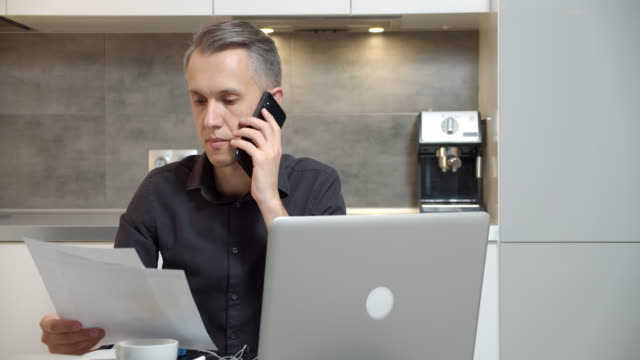 Young man reading a contract or report and talking on the phone at home. Handsome businessman working on laptop from home office.