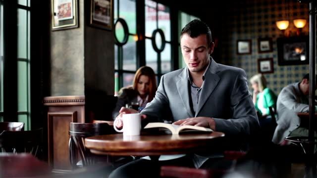 vídeos de stock e filmes b-roll de jovem ler livro em um café - bar local de entretenimento
