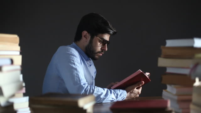 Young Man Reading Book On Desk video