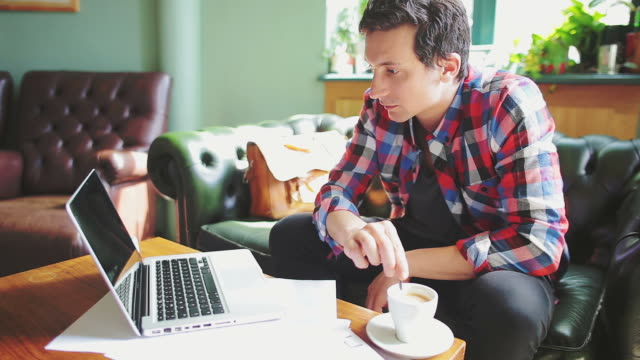 Young man reading on laptop in a coffee shop. Young man reading on laptop and stirring his coffee. small business saturday stock videos & royalty-free footage
