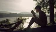 istock Young man relaxing by reading the book near lake 1304503972