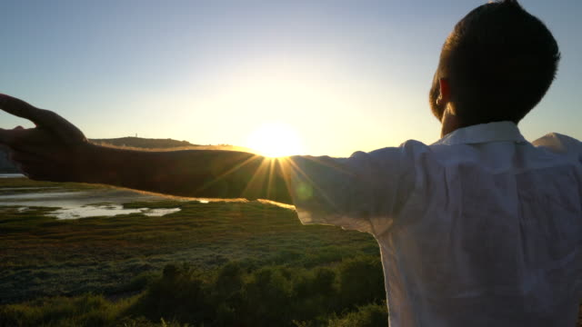 Young man relaxing by the sea, arms outstretched video