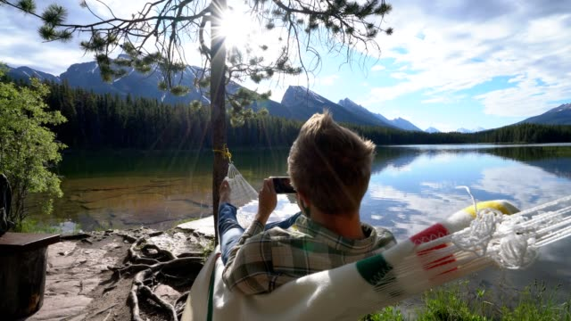 Young man relaxing on hammock with smart phone, Canada video