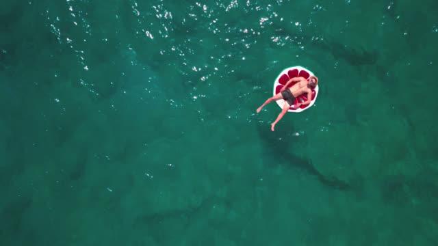 vídeos de stock, filmes e b-roll de homem novo que relaxa na melancia inflável no verão no mar - boia salva vidas