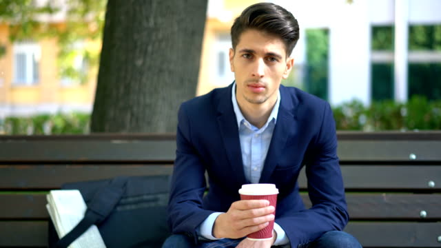 Young man relaxing with coffee on the park bench video