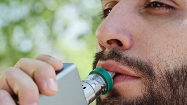 Young man relaxing with vaporizer: Vaping - Brief video