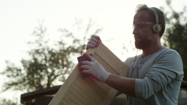 young man renovating old furniture - solo un uomo giovane video stock e b–roll