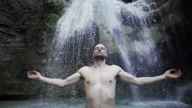 junger mann ruht unter wasserfällen - ein bad nehmen stock-videos und b-roll-filmmaterial