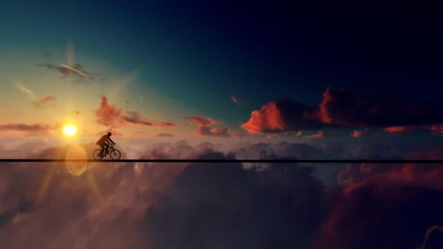 ung man befria en cykel på ett rep ovanför moln vid solnedgången - på gränsen bildbanksvideor och videomaterial från bakom kulisserna