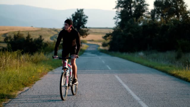 stockvideo's en b-roll-footage met jonge man rijdt een fiets op een landweg - 25 29 jaar