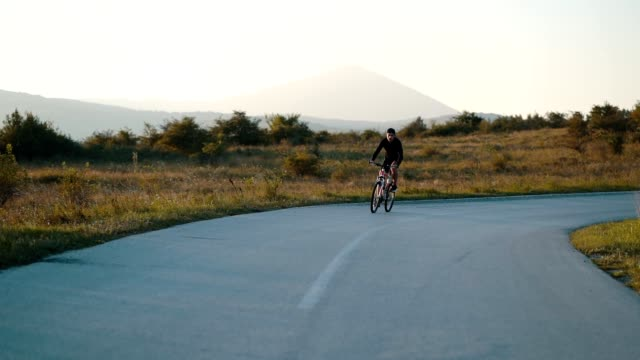 young man rides a bike on a country road - ciclismo su strada video stock e b–roll