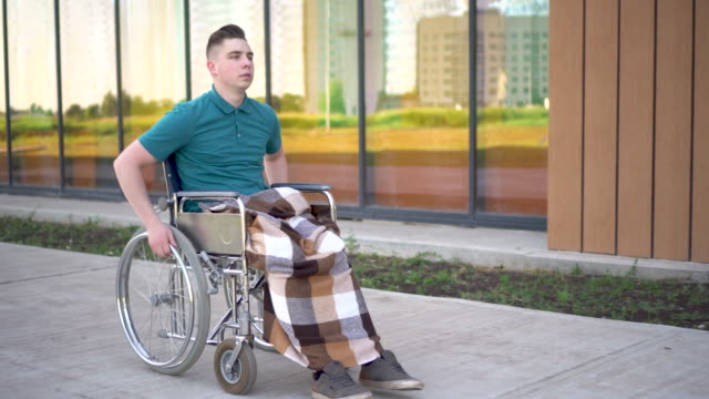 A young man rides a wheelchair and a heart attack occurs. A man in a wheelchair against the background of a glass building grabs his heart. Special transport for the disabled.