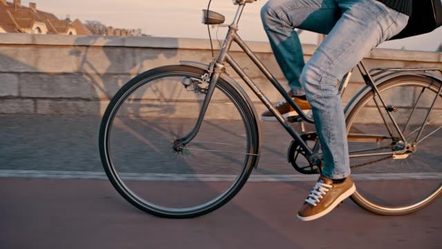 SLO MO Young man riding a bicycle across the bridge video