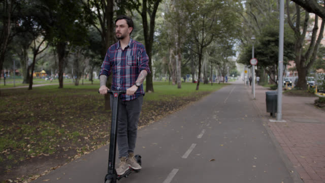 young man riding an electric scooter on the bicycle path - monopattino elettrico video stock e b–roll