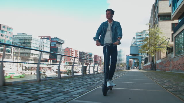 young man riding electric kick scooter on footpath - monopattino elettrico video stock e b–roll