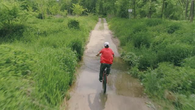 aerial young man riding his mountain bike through a puddle - percorso per bicicletta video stock e b–roll