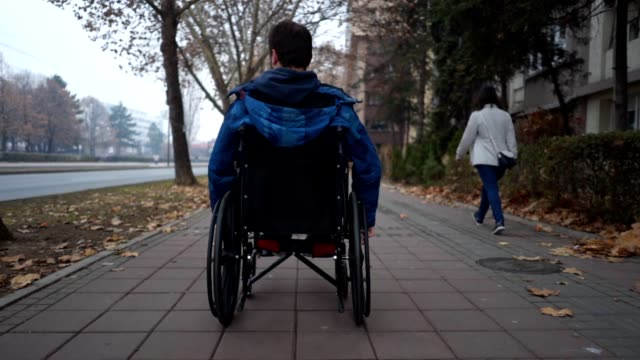 Young man riding in his wheelchair along sidewalk Young man riding in his wheelchair along sidewalk on a cold autumn day pushing wheelchair stock videos & royalty-free footage