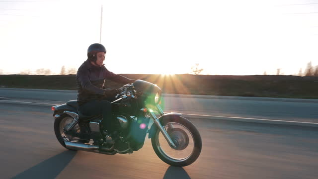Young man riding motorcycle on the road at sunset, slow motion video