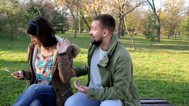 Hombre joven grosero coqueteando con la muchacha en el Parque - vídeo