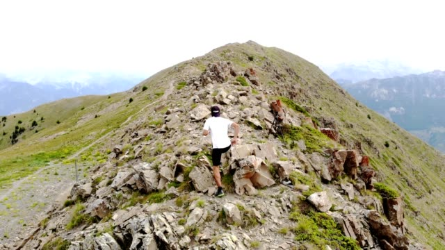 young man running on top of rocky mountain - trail, adrenaline sport - adrenalina video stock e b–roll
