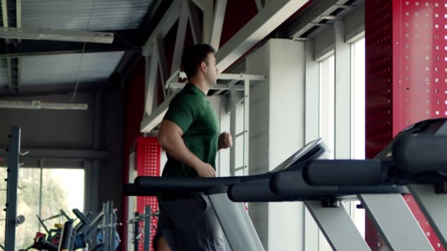 young man running on treadmill at gym, side view - runner rehab gym video stock e b–roll