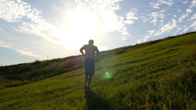 ung man kör över grön kulle över blå himmel bakgrund. manliga idrottare jogging i naturen vid solnedgången. sport löpare jogging uppförsbacke utomhus vid soluppgången med flare. cross-country utbildning. livsstil - jogging hill bildbanksvideor och videomaterial från bakom kulisserna