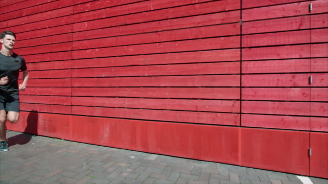 A young man running past a red wall in slow motion. video