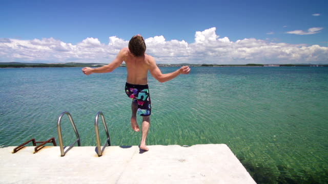 Young man runs and jumps in sea from a pier video