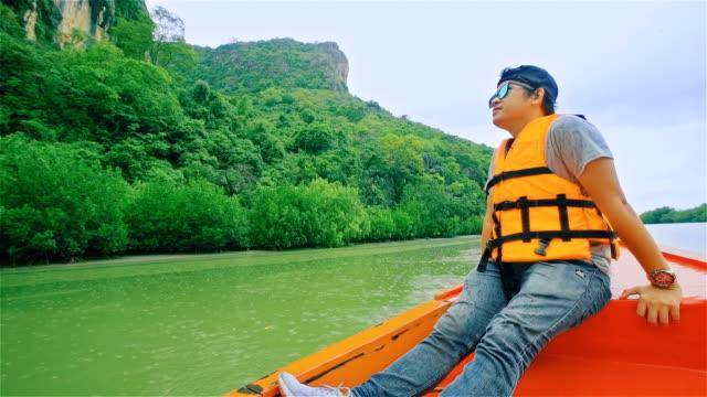 若い男はタイ南部のマングローブ林をロングテール タイ船でセーリング - 自然旅行点の映像素材/bロール