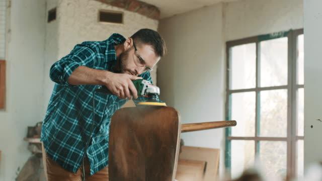 young man sanding a chair - solo un uomo giovane video stock e b–roll