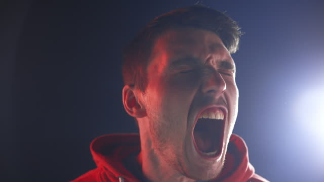 SLO MO LD Young man screaming loud Slow motion medium locked down shot of a young man screaming loud with his mouth wide open. Shot in Slovenia. mouth open stock videos & royalty-free footage