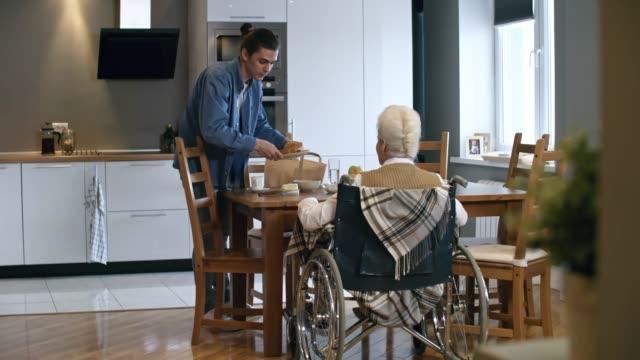 stockvideo's en b-roll-footage met jonge man serveert ontbijt voor senior lady - gezondheidszorg beroep