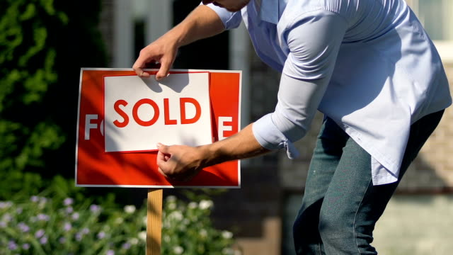 young man setting sold sign front of building, property sell service, ownership - vendere video stock e b–roll