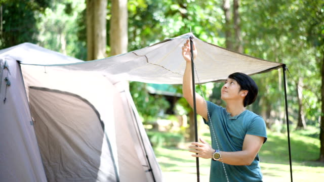Young man setting up tent in campsite.
