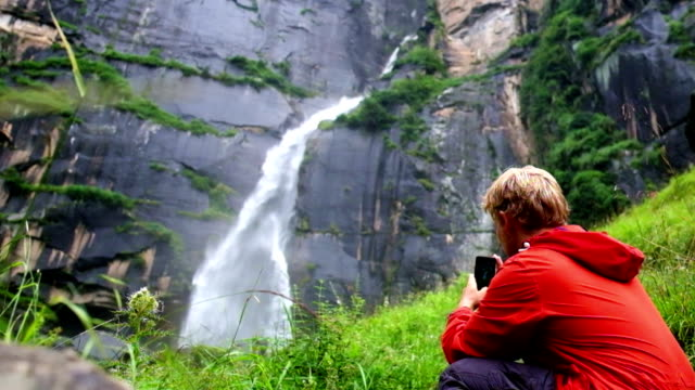 Young man shoots a video of a waterfall in the forest of India video