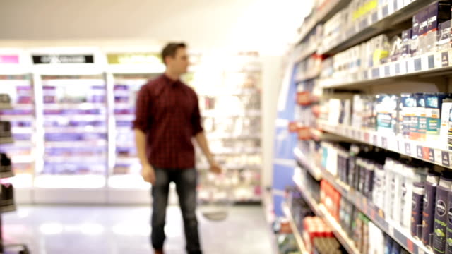young man shopping deodorant, panning shot - igiene video stock e b–roll